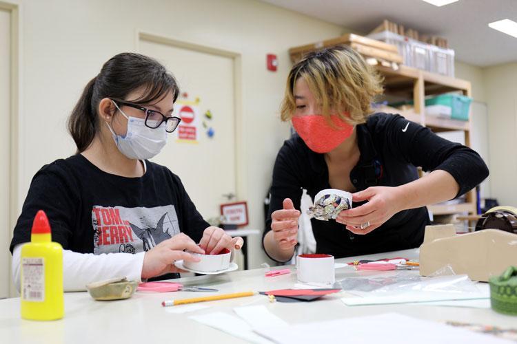 Saori Komura, right, an art instructor for the Camp Zama Arts and Crafts Center, helps Camryn Rosa, 11, make a washi paper box at Camp Zama, Japan, Jan. 23. (Photo Credit: Winifred Brown)