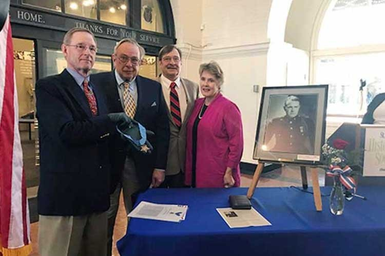 Courtney nephews unveil a replica of their Marine uncle's Medal of Honor on Nov. 12 at the St. Louis County Historical Society's Veterans' Memorial Hall in Duluth, Minn. From left, Courtney Storey, Ben Storey, Bob Storey and his wife, Lynn Storey. (COURTESY OF THE ST. LOUIS COUNTY HISTORICAL SOCIETY)