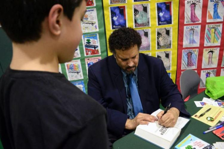 Bestselling author Neal Shusterman signs a copy of one of his books for a sixth-grader during Shusterman's visit to Yokosuka Middle School, Japan, Thursday, Jan. 31, 2019. (CHRISTIAN LOPEZ/STARS AND STRIPES)