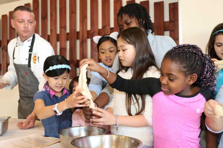 Youth members of the Cooking Club at the Sagamihara Family Housing Area School Age Center put their hands on fresh pizza dough they made together Jan. 30 at the SHA Club's Pacific Rim restaurant. The club members were there to learn how to make pepperoni pizza from scratch, and they later ate their own creations. (Photo Credit: Noriko Kudo, U.S. Army Garrison Japan Public Affairs)