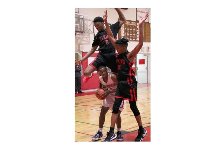 E.J. King's Dyson Robinson leapfrogs Nile C. Kinnick's Rodrick Bell while Cobras teammate Isaiah Williams watches during Friday's DODEA-Japan Tournament boys final. The Red Devils won 73-53. (EMMANESTA STOVALL/SPECIAL TO STRIPES)