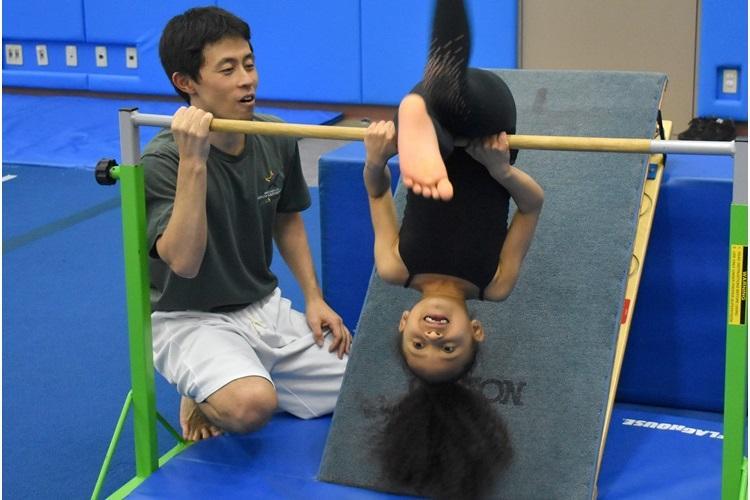 Bella Adams, 6, practices gymnastics on a bar as Yosuke Kinoshita, gymnastics instructor, supervises at the Camp Zama Community Recreation Center Feb. 12 during a SKIES Unlimited gymnastics class. (Photo Credit: Wendy Brown, U.S. Army Garrison Japan Public Affairs)