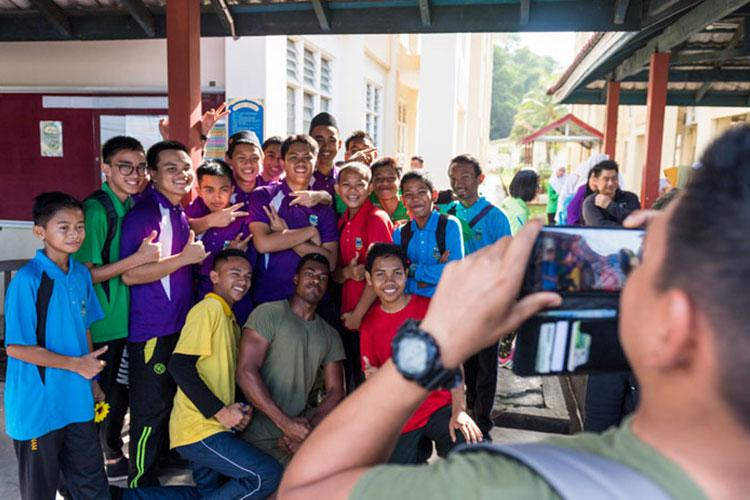 KOTA KINABALU, Malaysia (Feb. 25, 2019) – Lance Cpl. Daniel Notice, from Florissant, Miss., with the 31st Marine Expeditionary Unit (MEU) poses with students from the Sekolah Menengah Kebangsaan Inanam High School during a cultural exchange and community service event. (Photo by Petty Officer 2nd Class Markus Castenda)