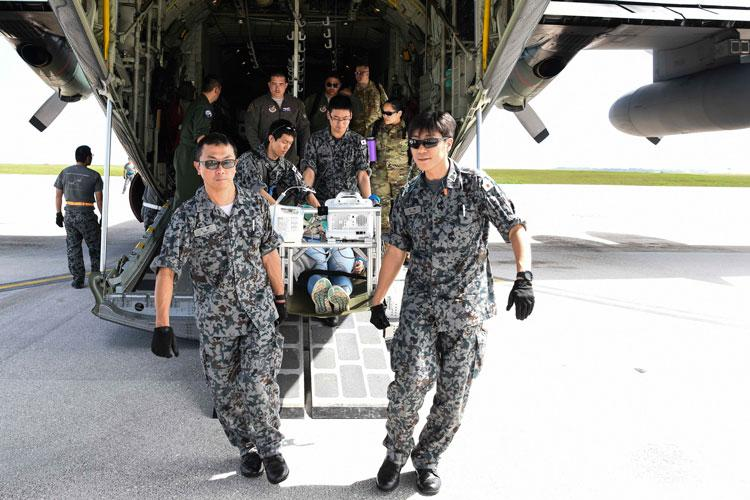 Medical service members from the Japan Air Self-Defense Force perform simulated emergency medical care and transportation on U.S. Airman 1st Class Kelly Destiny, 36 Mobility Response Squadron Air Transportation apprentice, during an exercise scenario for Cope North 2019, Feb. 27, 2019, at Andersen Air Force Base, Guam. (U.S. Air Force photo by Tech. Sgt. Jake Barreiro)
