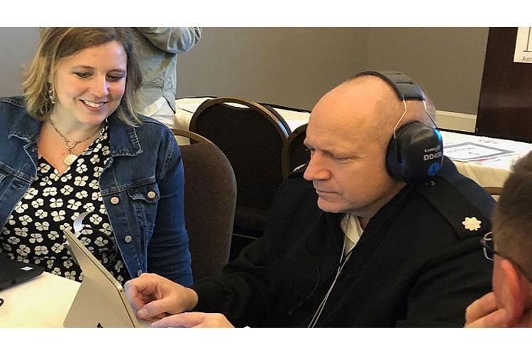 Lt. Col. John Merkley, Army Public Health Center, tests out a boothless audiometry headset system, one of four systems demonstrated by manufacturers during a workshop hosted by the DoD Hearing Center of Excellence at this year's National Hearing Conservation Association Conference. (HCE photo)