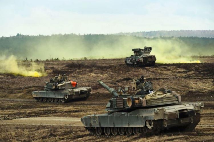 M1A2 Abrams tanks and Bradley Fighting Vehicles converge on a smoke signal during a live-fire exercise at Grafenwoehr, Germany, in March. President Trump is pushing a plan that demands allies pick up the full cost of hosting U.S. troops in their countries, plus a 50 percent premium for American protection, according to a news report. (MARTIN EGNASH/STARS AND STRIPES)