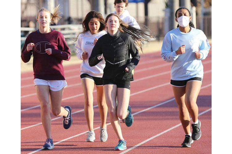 Yokota distance runners Anneliese Schneider, Emi Dashler, Aiko Galvin and Siu Davis go through their practice paces. In the background is boys distance runner Mickey Galvin. (GREG HOLLADAY/SPECIAL TO STRIPES)