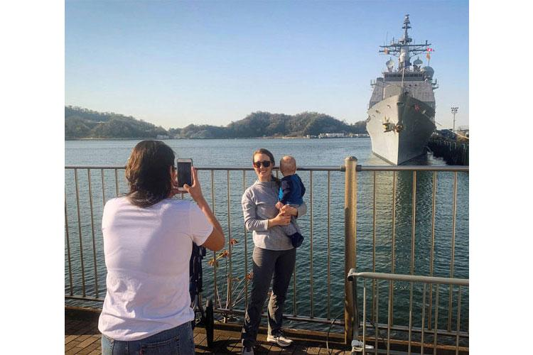 Ashton Andrews and her son, Thomas, pose for a photo with their husband and father, Lt. Cmdr. Ryan Andrews, waving far in the distance on the USS Antietam, at Yokosuka Naval Base, Japan, Thursday, March 26, 2020. (CAITLIN DOORNBOS/STARS AND STRIPES)