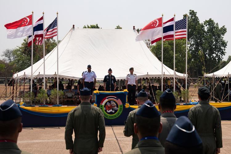 U.S. Air Force Gen. CQ Brown Jr., Pacific Air Forces commander, Royal Thai Air Force Air Chief Marshal Chaiyapruk Didyasarin, commander-in-chief, and Republic of Singapore Air Force Brigadier General Tommy Tan Ah Han, chief of staff–air staff, stand at attention during the closing ceremony of COPE Tiger 2019 at Korat Royal Thai Air Force Base, Thailand, March 22, 2019. (U.S. Air Force photo by Staff Sgt. Melanie A. Hutto)