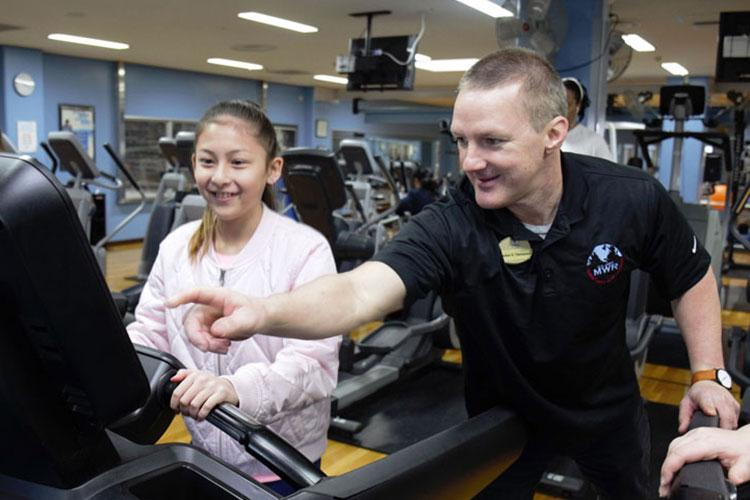 Stefan Thompson, right, director of Sports, Fitness and Aquatics at Yano Fitness Center, shows Kellis Eisenhauer, a sixth-grader at John O. Arnn Elementary School, how to check her heart rate as she runs on a treadmill during a job shadowing event at Camp Zama April 4. (Photo Credit: Photo by Dustin Perry, U.S. Army Garrison Japan)