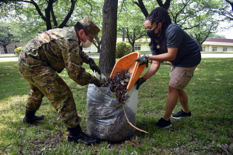 Sgt. Jennifer Jackson, right, Camp Zama's Better Opportunities for Single Soldiers president, and 1st Lt. Naoki Kumagai, assigned to the 4th Engineer Group, Japanese Ground Self-Defense Force, work together to clean up the area around the Otakebi torii during a BOSS community outreach initiative at Camp Zama, Japan, May 27. (Photo Credit: Winifred Brown)