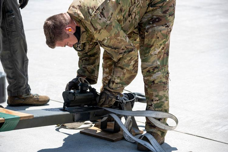 U.S. Air Force Tech. Sgt. Matthew Fry, a 36th Airlift Squadron C-130J Super Hercules loadmaster instructor, attaches a tie-down strap to a piece of equipment prior to loading it onto a C-130J at Misawa Air Base, Japan, May 28, 2020. (U.S. Air Force photo by Melanie A. Bulow-Gonterman)