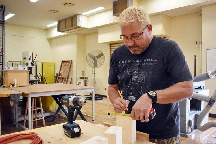 Wayne Hatfield prepares to drill a hole in a candleholder at the Camp Zama Arts and Crafts Center's woodshop at Camp Zama, Japan, June 24. (Photo Credit: Winifred Brown)