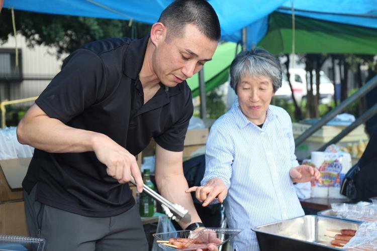 Staff Sgt. David Shores, left, assigned to the 38th Air Defense Artillery Brigade, grills hot dogs at a festival July 14 at Aioi Park near Sagami General Depot. Four Soldiers from the 38th ADA volunteered to provide support at the festival as a way to reinforce the relationship the Army shares with its nearby neighbors outside the gate at Sagami Depot. (Photo Credit: Noriko Kudo, U.S. Army Garrison Japan Public Affairs)