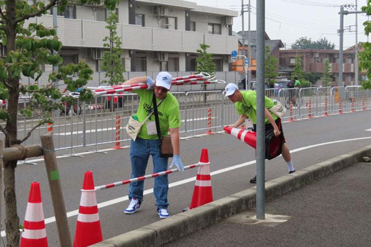 Gary Ledbetter, left, an employee at Camp Zama's Army Community Service, and Spc. Christopher Keeling, assigned to the 35th Combat Sustainment Support Battalion, right, set up road cones and barriers during the 2020 Tokyo Olympics' cycling road race pre-trial event July 21 in Sagamihara City, through which a 19-mile segment of the men's 152-mile and women's 92-mile race will run next year. (Photo Credit: U.S. Army photo by Sayuri Nagai, U.S. Army Garrison Japan Public Affairs)