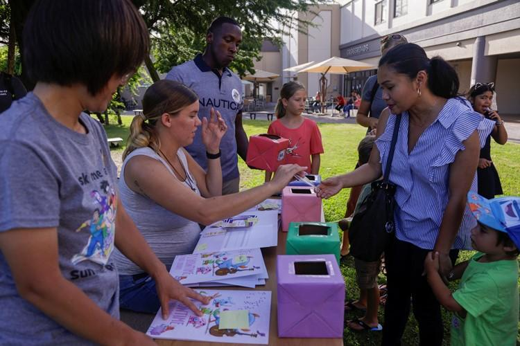 Families enter in a raffle during a Summer Reading Party hosted by Marine and Family Programs at Marine Corps Air Station Iwakuni, Japan, August 7, 2019. The party was held to celebrate all of the reading the children accomplished over the span of six weeks. The party included a raffle giveaway, live music, food and drinks. (U.S. Marine Corps photo by Pfc. Triton Lai)