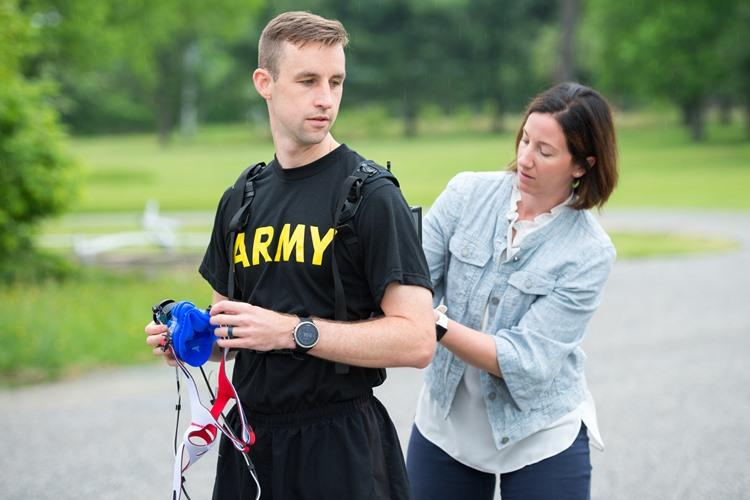 Megan Amadeo, Army Wellness Center Project Officer, Army Public Health Center, assists U.S. Army Capt. Zachary Schroeder, Headquarters and Headquarters Company commander, Army Public Health Center, with putting on the new K5 metabolic testing unit May 9, 2019, as part of his training to compete in the Army Ten Miler in Oct. 2019. (Photo Credit: Graham Snodgrass)