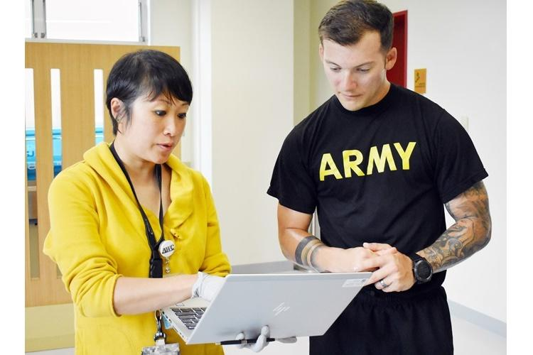 Shannon Vo, left, a health educator at the Camp Zama Army Wellness Center, discusses fitness test results with Staff Sgt. Josh Beysselance, assigned to the 78th Signal Battalion, at the Yano Fitness Center at Camp Zama, Japan, Aug. 14. (Photo Credit: Wendy Brown, U.S. Army Garrison Japan Public Affairs)