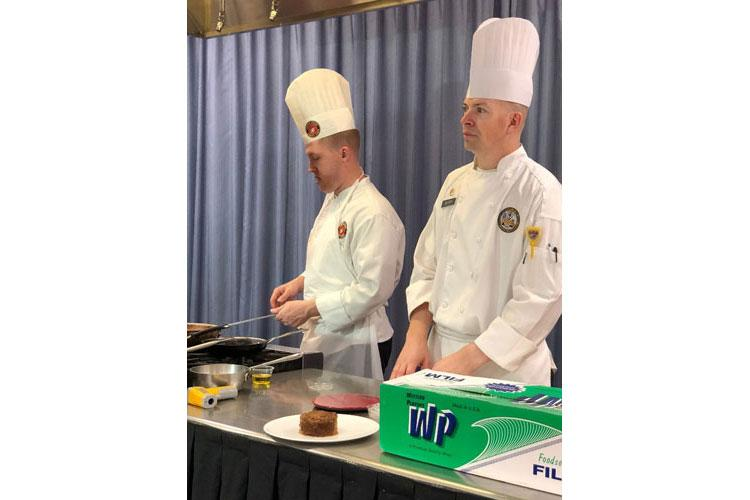 Marine Gunnery Sgt. Tavis McGregor (left) and Army Staff Sgt. Adam Berry, advance culinary instructors, prepare a recipe during filming at the Joint Culinary Center of Excellence on Fort Lee, Virginia. (DeCA photo: Stephen Settles)
