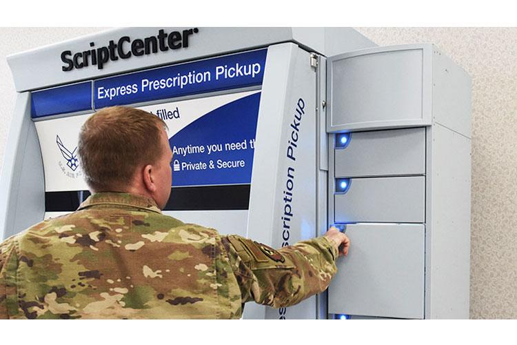 Staff Sgt. Dustin Stevens, 7th Medical Support Squadron pharmacy technician, opens a locker in the ScriptCenter at Dyess Air Force Base, Texas, Feb. 26, 2020. Larger refill prescription orders will be available in the lockers beside the machine. (U.S. Air Force photo by Senior Airman Mercedes Porter)