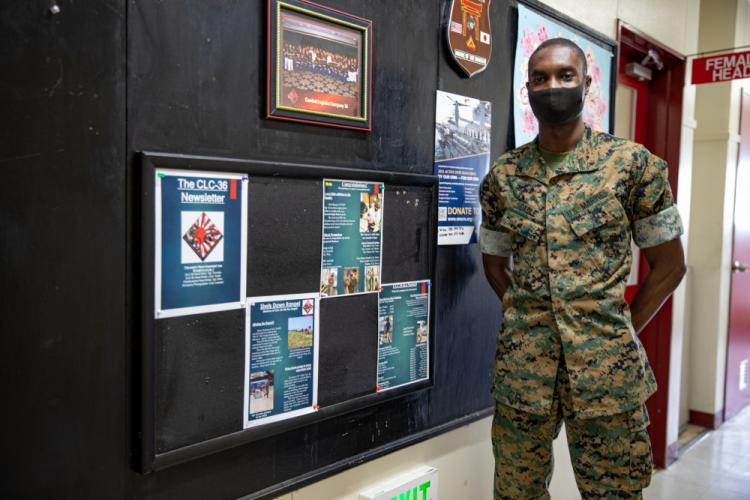 U.S. Marine Lance Cpl. Raynel Cadle, a property clerk and newsletter editor with Combat Logistics Company (CLC) 36, poses with his latest newsletter aboard Marine Corps Air Station (MCAS) Iwakuni, Japan, March 22, 2021. Cadle updates Marines at CLC-36 about the past, current, and future events through his newsletter that he publishes weekly. (U.S. Marine Corps photo by Lance Cpl. Trista Whited)