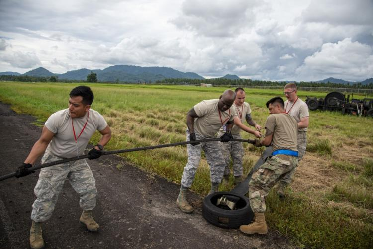 U.S. Air Force Airmen from the 35th Civil Engineer Squadron, Misawa Air Base Japan pull the mobile aircraft arresting system (MAAS) cable across the runway at the Sam Ratulangi International Airport, Manado, Indonesia, June 17, 2019. Six MAAS technicians forward deployed to Indonesia to provide support for Cope West 19.The MAAS is designed to ensure pilots land and take-off safely in the event of an in-flight emergency. (U.S. Air Force photo by Staff Sgt. Melanie A. Hutto)
