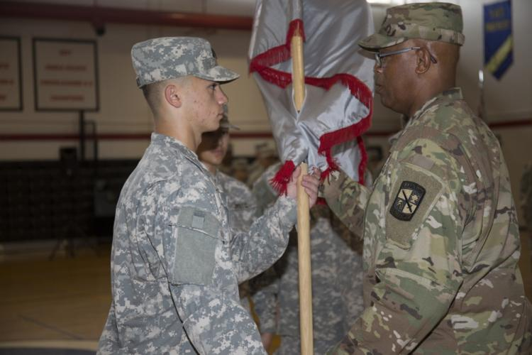 "Retired Lt. Col. Douglas Fields, right, a Zama JROTC instructor, passes the guidon to Cadet Lt. Col. Maxwell Orlosky, a junior at Zama American Middle High School, the incoming ""Trojan"" Battalion commander, during a change-of-command ceremony held May 14 at ZAMHS on Camp Zama, Japan."