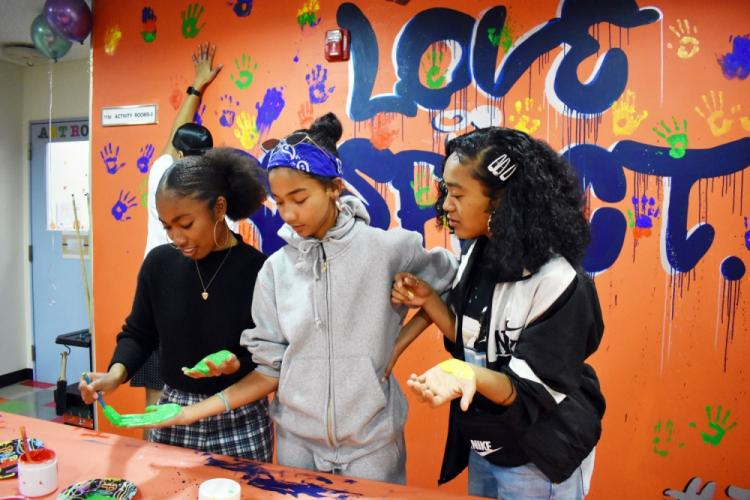 "From left, Midori Robinson, Kyleigh Rose and Keisha McNeill paint their hands so they can put a handprint on the ""Love is Respect"" mural during the Camp Zama Youth Center Teen Dating Violence Awareness Lock-In at Camp Zama, Japan, Feb. 7, 2020."