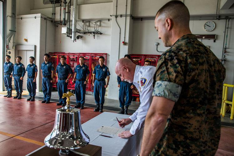 U.S. Marine Corps Col. Fredrick Lewis, Marine Corps Air Station (MCAS) Iwakuni commanding officer, and John Neville, installation fire chief, sign the fire prevention proclamation on MCAS Iwakuni, Japan, September 27, 2019. Fire Prevention Week's purpose is to prepare MCAS Iwakuni residents for potential fires. (U.S. Marine Corps photo by Lance Cpl. Trista Whited)