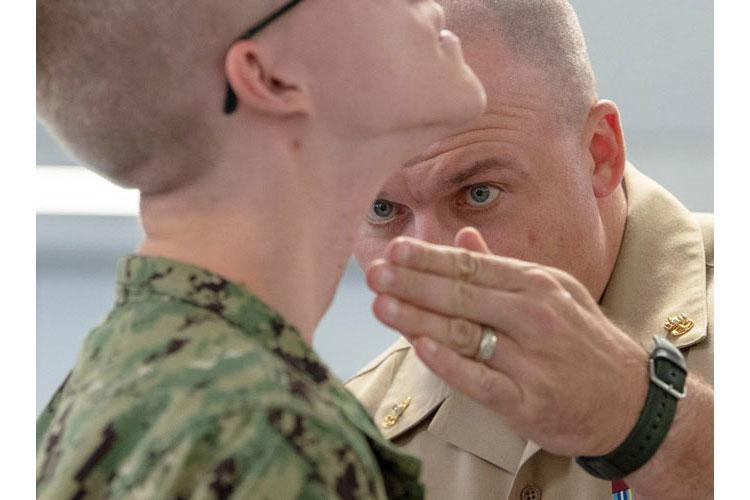 In an October, 2018 file photo, Chief Operations Specialist James Conyne, a recruit division commander, inspects the quality of a recruit's shave before a personnel inspection inside a compartment in the USS Kearsarge barracks at Recruit Training Command in Great Lakes, Ill. (SPENCER FLING/U.S. NAVY)