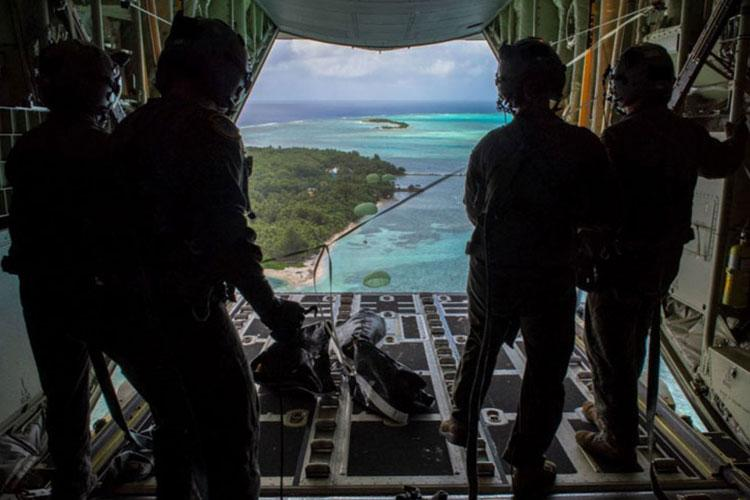 Loadmasters with the 36th Airlift Squadron out of Yokota Air Base, Japan, watch as the four Low-Cost, Low-Altitude humanitarian assistance bundles they just airdropped parachute down to those in need during Operation Christmas Drop 2019, at Nomwin, Federated States of Micronesia, Dec. 13, 2019. (U.S. Air Force photo by Senior Airman Matthew Gilmore)