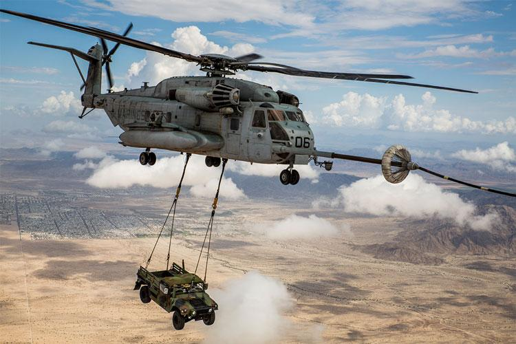 A U.S. Marine Corps CH-53E Super Stallion aircraft assigned to Marine Aviation Weapons and Tactics Squadron One (MAWTS-1) conducts an aerial refuel with a KC-130J Hercules aircraft during Weapons and Tactics Instructor (WTI) course 1-19 at Marine Corps Air Station Yuma, Arizona. (U.S. Marine Corps photo by Sgt. Takoune H. Norasingh)