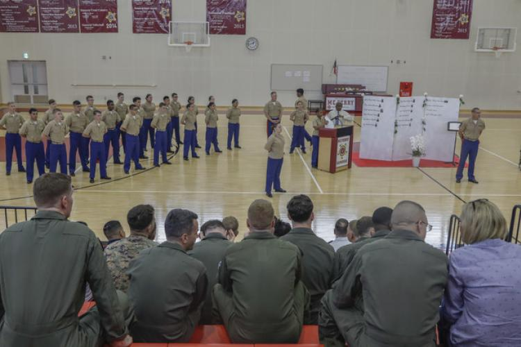 Service members attend a Memorial Day ceremony at Marine Corps Air Station Iwakuni, Japan, May 20, 2019. The ceremony was coordinated by the school's JROTC program in order to honor the memories of fallen service members. U.S. Marines from Marine All-Weather Fighter Attack Squadron (VMFA) 242 and Marine Aerial Refueler Transport Squadron (VMGR) 152 attended the ceremony to commemorate the memories of their fellow Marines on the memorial wall. (U.S. Marine Corps photo by Pfc. Triton Lai)