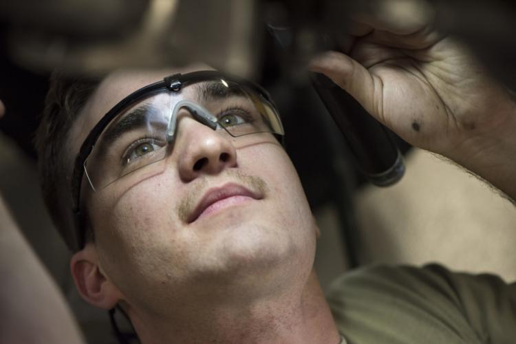 U.S. Air Force Airman 1st Class Tyler Bednar, a 35th Maintenance Squadron aerospace propulsion journeyman, inspects the underbelly of an engine with a flashlight at Misawa Air Base, Japan, July 16, 2019. The shops leadership described the Airmen of the 35th MXS propulsions centralized repair facility as flexible, selfless, inspiring and hard-working. (U.S. Air Force photo by Senior Airman Collette Brooks)