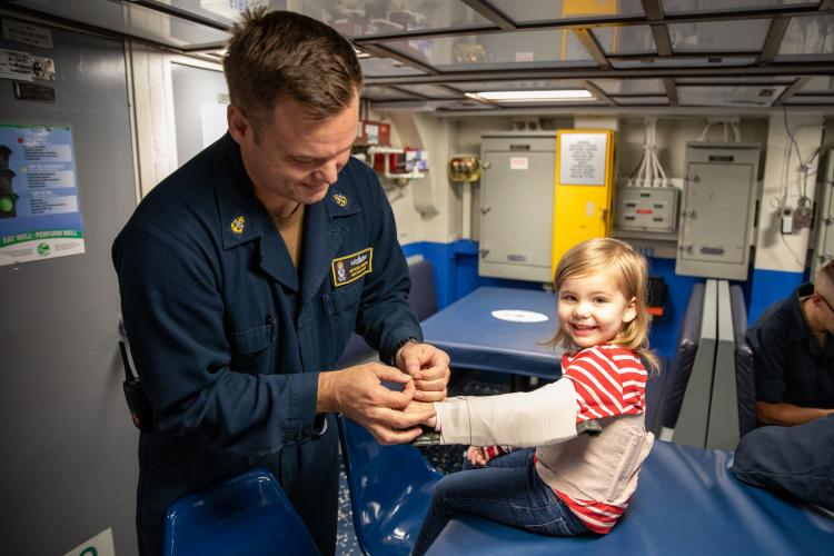 SASEBO, Japan (November 01, 2019) Chief Hospital Corpsman, Kenneth Van Tassel, bandges up his daughter for fun to show her what he does at work aboard Avenger-class mine countermeasures ship USS Pioneer (MCM 9). Pioneer, part of Mine Countermeasures Squadron 7, is operating in the 7th Fleet area of operations to enhance interoperability with partners and serve as a ready-response platform for contingency operations. (Photo by Lt.j.g. Alexander Fairbanks)