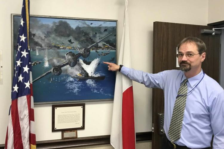 "Greg Mattson, the 5th Air Force historian, shows off a painting in the unit headquarters that depicts a World War II exploit of Col. Paul Irvin ""Pappy"" Gunn on Sept. 11, 2019. SETH ROBSON/STARS AND STRIPES"