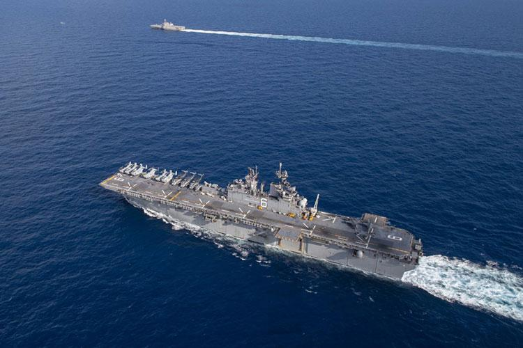 SOUTH CHINA SEA (March 13, 2020) Amphibious assault ship USS America (LHA 6) sails alongside littoral combat ship USS Gabrielle Giffords (LCS 10). America, flagship of the America Expeditionary Strike Group, 31st Marine Expeditionary Unit team, is operating in the U.S. 7th Fleet area of operations to enhance interoperability with allies and partners and serve as a ready response force to defend peace and stability in the Indo-Pacific region.