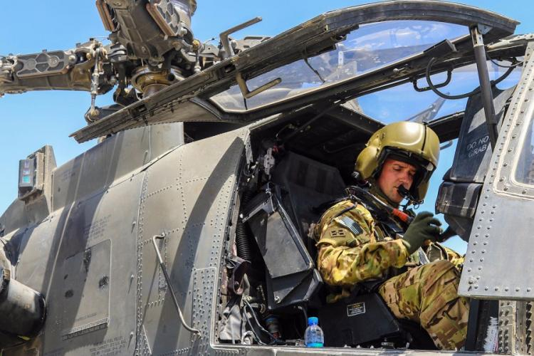 A U.S. Army AH-64 Apache pilot conducts final preflight checks before taking off in Afghanistan in April 2019. The Army announced new bonuses for pilots to try to keep them from being lured away by higher pay and better benefits paid by commercial airlines. ROXANA THOMPSON/U.S. ARMY