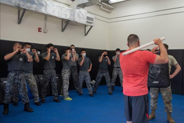 Staff Sgt. Joshua Cordova, 374th Security Forces Squadron flight sergeant, demonstrates a baton technique to Koku-Jieitai (Japan Air Self-Defense Force) members during the bilateral aircraft security training at Yokota Air Base, Japan, August 7, 2020. Koku-Jieitai Security personnel from across Japan took part in the bilateral training event with the 374th SFS. (U.S. Air Force photo by Machiko Airta)