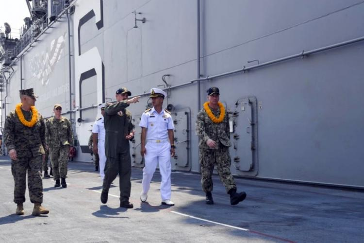U.S. Navy Cmdr. Stephen Audelo, pointing, guides Royal Thai Navy Capt. Arpa Chapanon during a tour of the amphibious assault ship USS America in Laem Chabang, Thailand, Feb. 22, 2020. VANCE HAND/U.S. NAVY