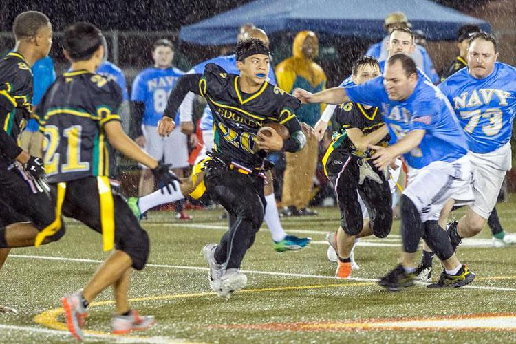 Senior Douglass Tackney, with ball, and his Robert D. Edgren teammates played flag football in the driving rain against Navy sailors at Misawa for their homecoming game. (Jason Wysong/Special to Stripes)