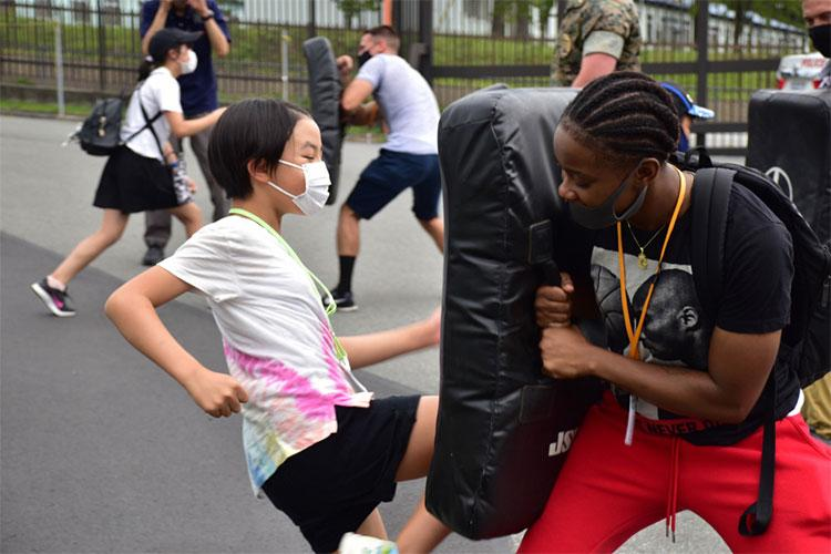A local Japanese child practices kicking a training pad held by Sgt. Takiyah Wesley, Combined Arms Training Center Camp Fuji supply sergeant, Aug. 7, 2021, Shizuoka, Japan. Marines and Sailors from the installation volunteered at the National Chuo Youth Friendship Center's fifth annual English camp, where they engaged local children in conversation and activities. Wesley is a native of Memphis, Tennessee. (U.S. Marine Corps photo by Katie Gray)