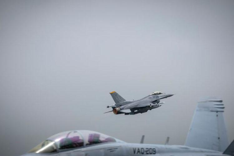 A U.S. Air Force F-16 Fighting Falcon flies over a U.S. Navy EA-18G during a PACIFIC WEASEL exercise at Misawa Air Base, Japan, June 19, 2020. This exercise allowed the 35th Operations Group and the U.S. Navy Electronic Attack Squadron 209 (VAQ-209) to integrate and enhance interoperability. (U.S. Air Force photo by Airman 1st Class China M. Shock)