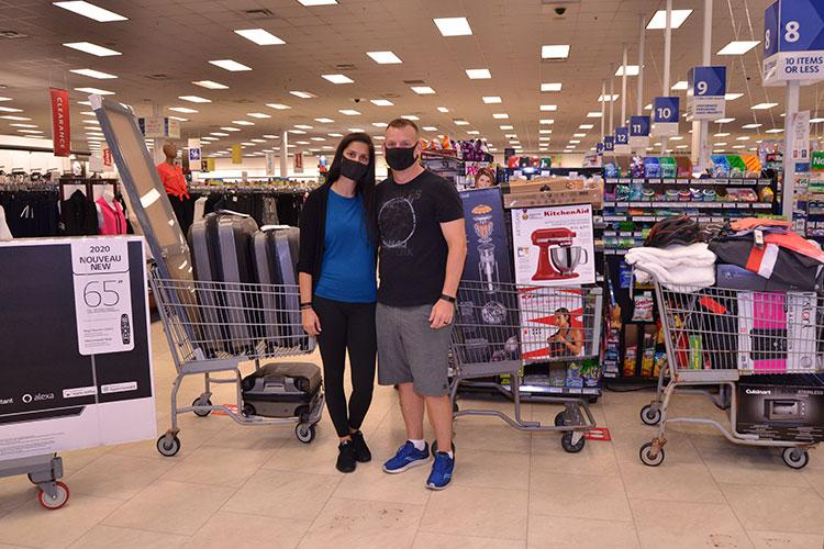 On Aug. 29, Master Sgt. Jacob Hayes, communications chief for 3rd Supply Battalion on Camp Kinser, poses with his wife, Jessica at the checkout line at the end of their Rip, Sip, and Ultimate Trip $10,000 Exchange shopping spree. (U.S. Army Photo by Staff Sgt. Mark A. Kauffman)