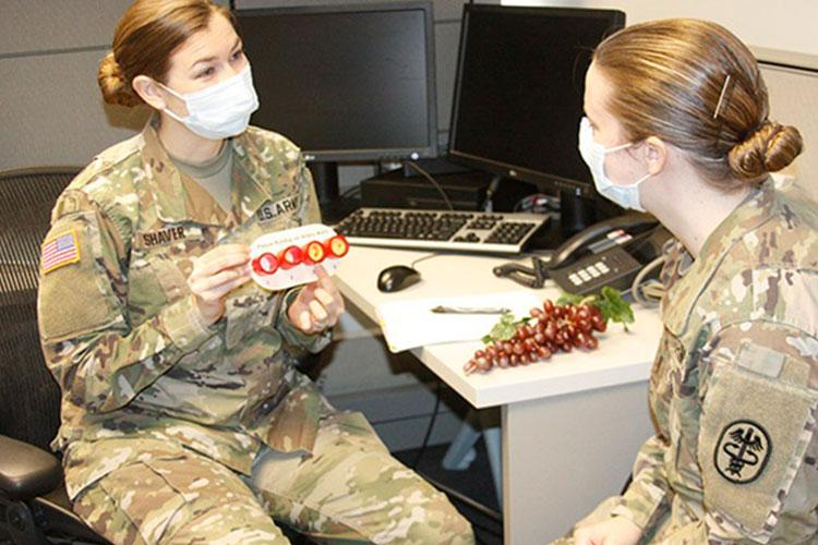 Army 1st Lt. Caitlyn Shaver and Army 1st Lt. Brittany Powers, dietetic interns at Walter Reed National Military Medical Center, role play a nutrition consultation as part of their training in Phase 2 of the U.S. Military-Baylor Graduate Program in Nutrition at WRNMMC (Photo by: Bernard Little, Walter Reed National Military Medical Center).