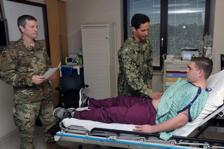 U.S. Air Force Maj. Mark Lytle, vascular surgeon at Eglin Air Force Base's 96th Medical Group, observes orthopedic surgeon Lt. Andrew Wright's examination of Petty Officer 3rd Class Kyle Benson during simulation at Naval Hospital Pensacola on Jan. 31, 2019.  BRANNON DEUGAN/U.S. NAVY