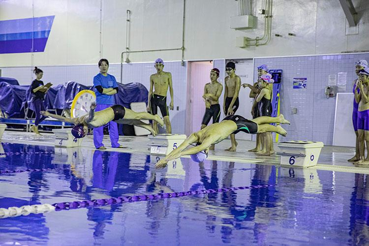 Swimmers dive into the water during a relay at IronWorks Gym Pool, Marine Corps Air Station (MCAS) Iwakuni, Japan, February 16, 2020. The Tsunamis, the MCAS Iwakuni Schools' swim team hosted a friendly swim meet with Ocean Swim team, the local Iwakuni City swim team, in order to foster their friendship in sports. (U.S. Marine Corps photo by Lance Cpl. Triton Lai)