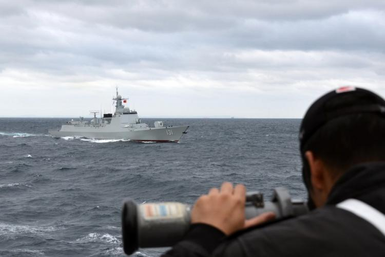 A member of the Japan Maritime Self-Defense Force working aboard the destroyer JS Samidare looks at the Chinese guided-missile destroyer Taiyuan during a joint exercise south of Japan last week. JAPAN MARITIME SELF-DEFENSE FORCE