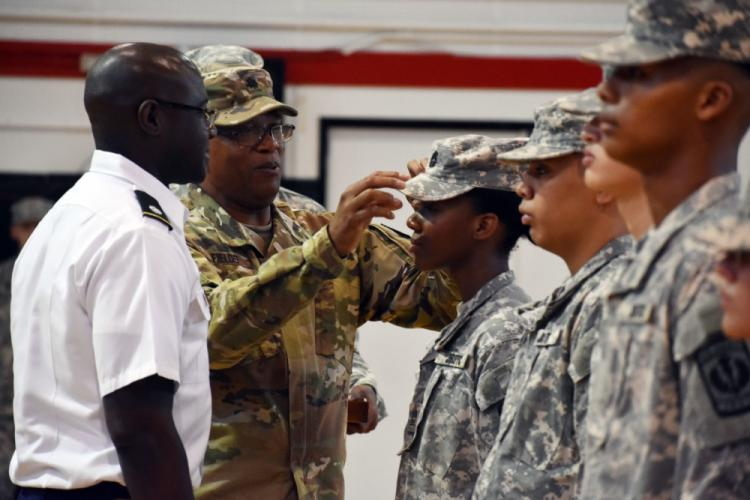 Retired Lt. Col. Douglas Fields, senior Army instructor for the Junior Reserve Officers' Training Corps at Zama Middle High School, promotes Queen Thomas, a sophomore at the school, to the rank of cadet master sergeant during a promotion ceremony at Camp Zama, Japan, Oct. 3, 2019. Thomas' father, Lt. Col. Demetrick Thomas, right, commander, 35th Combat Sustainment Support Battalion, looks on.