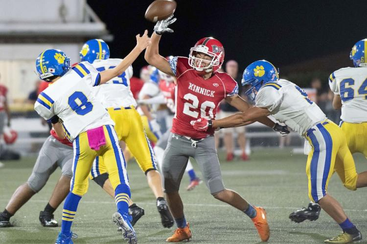 Nile C. Kinnick's Anthony Santos, rushing Yokota quarterback Brody Choate's throw, had seven tackles for the Red Devils. JIMMY MILLS/SPECIAL TO STRIPES